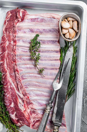 Raw uncooked rack of mutton lamb ribs in baking dish. White background. Top view Фото со стока