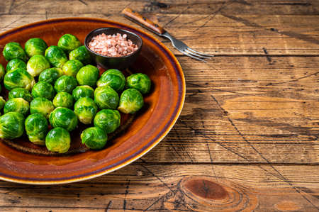 Cooked Brussels green sprouts cabbage in a rustic plate with salt. wooden background. Top view. Copy space