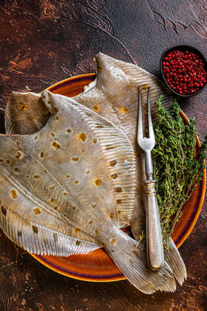 Raw flounder or plaice on rustic plate with herbs. Dark background. Top view