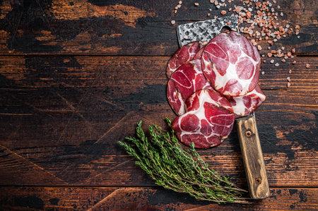 Coppa, Capocollo, Capicollo Cured ham on meat cleaver. Dark wooden background. Top view. Copy space