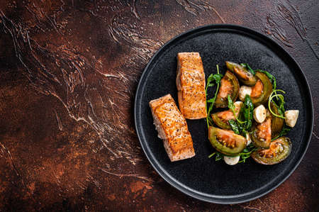 Grilled Salmon Fillet Steaks with arugula and tomato salad on a plate. Dark background. Top view. Copy space
