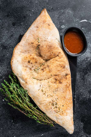 Calzone closed pizza with ham and cheese. Black background. Top view