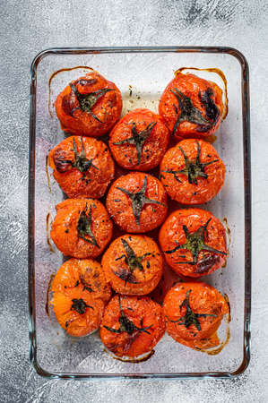 Baked cherry tomatoes with olive oil and thyme in baking dish. White background. Top view Фото со стока