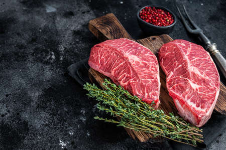Fresh Raw Top Blade or flat iron beef meat steaks on a butcher cutting board. Black background. Top View. Copy space