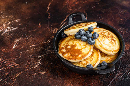 Fried Pancakes with fresh blueberries and maple syrup in a pan. Dark background. Top View. Copy space