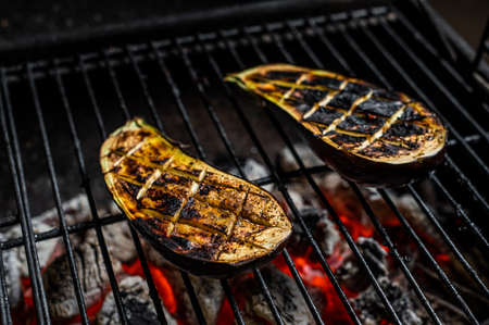 Eggplant on barbecue, outdoor BBQ grill with fire. Top view