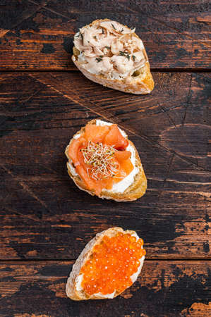 Bruschetta with Hot Smoked salmon, red caviar and herbs. Wooden background. Top view