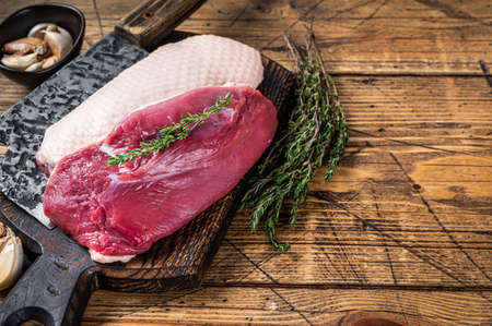 Fresh Raw Duck breast fillet steaks on butcher board with meat cleaver. wooden background. Top View. Copy space