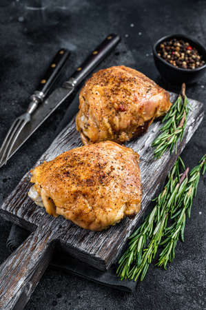 Spicy Bbq grilled chicken thighs on a wooden board with rosemary. Black background. Top View