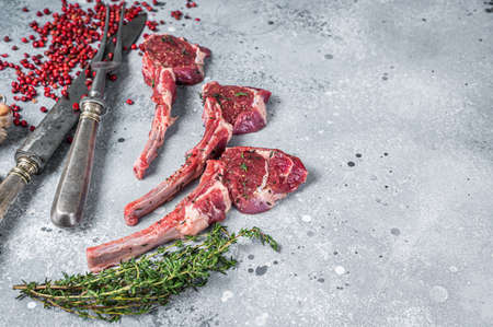 Uncooked lamb meat chops steaks on a butcher table with pepper and thyme. Gray background. Top view. Copy space Фото со стока