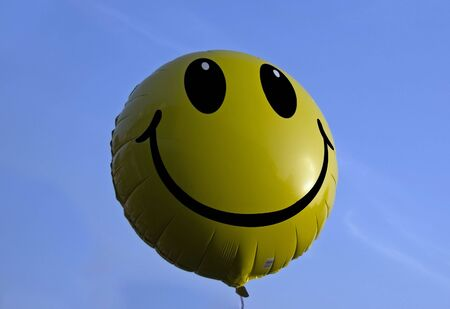 a yellow oker smiling balloon in the blue sky Stock Photo - 4621148