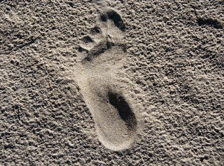 A single footstep printed in the sand on the beach, walking to somewhere photo