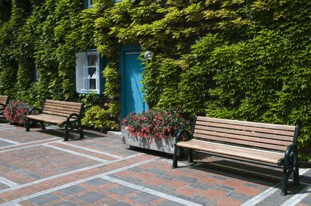 place to sit and relax in park with blue door between the green wall photo