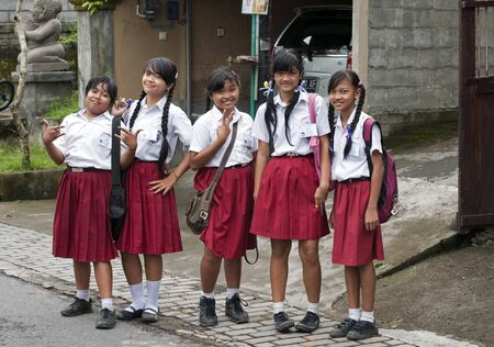 UBUD - 5 April 2011: Young school girls in uniform on the stret having fun on April 5, 2011 on Ubud street on Bali, Indonesia  Stock Photo - 9338368