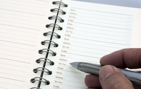 adress: man writing in the agenda telephone numbers and email adress Stock Photo