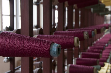 textile industry: old loom with pink red cotton Editorial