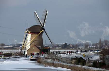 people skating in front of windmill Holland photo
