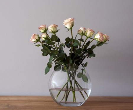glass vase: bouquest of roses in a vase on wooden table
