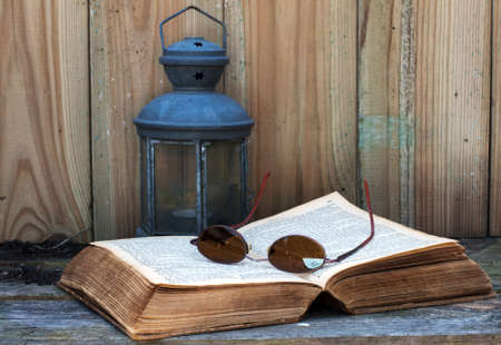 still life with old bible light and glasses photo