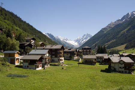 typical Switsch houses with the mountains and snow as a background photo