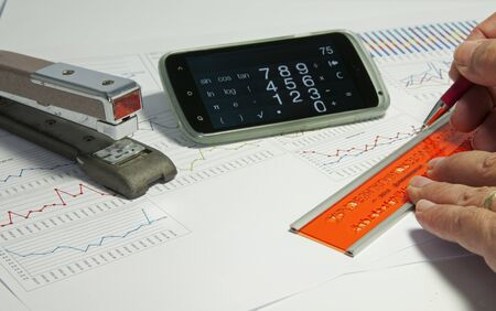 estimating: man making diagrams and graphics on  a table with calculator and stapler