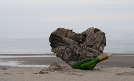 green bottle post and a lost heart on the beach photo