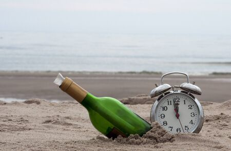 green bottle post and a clokc on the beach photo