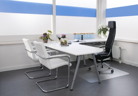 private hospital: clean white office in hospital with flowers laptop and phone Stock Photo