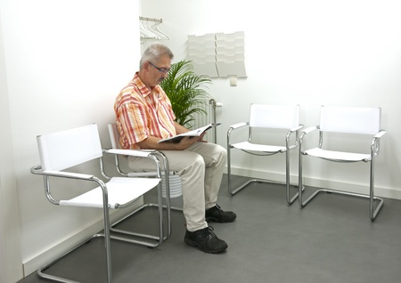 adult male reading a book and sitting in waiting room photo