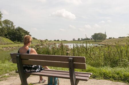woman on wooden seat looking over the dutch landscape of veere Stock Photo - 15052347