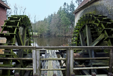 old waterwheel for generating green energy from water falling photo