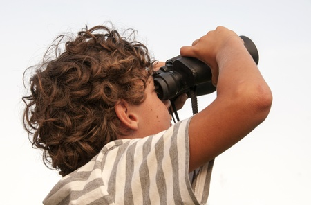 young boy with binoculars looking at the sky photo