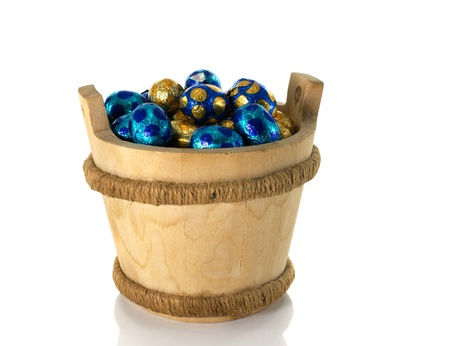 wooden bucket with easter eggs isolated on white Stock Photo - 17452526