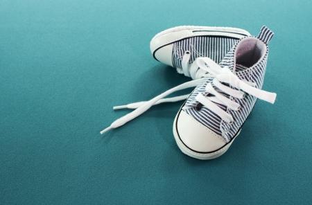 pequeños zapatos de bebé del deporte en el fondo azul Foto de archivo