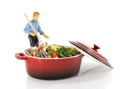 plastic model man stir vegetarian food in red saucepan photo