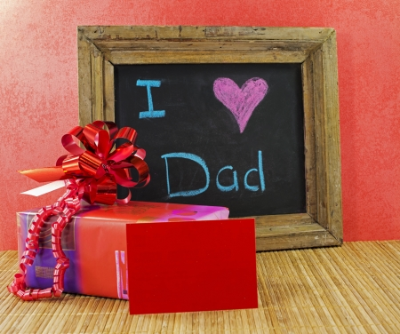 father's day: happy fathers day with present and blackboard with text i love dad Stock Photo