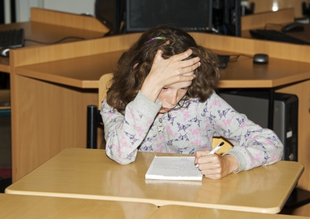 proble: left handed girl writing on paper in school