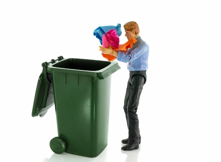 reusing: man throw old paper in green container