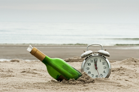 message in bottle on the beach with alarm clock photo