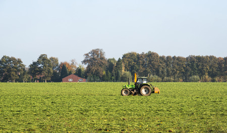 farmer with tractor on the green field photo