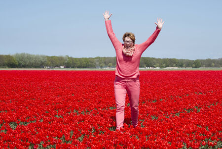 jubilate: adult woman happy  in red tulip field in Holland near Lisse Stock Photo