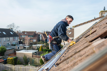 solar roof: man making the construction for the solar panels high on the roof