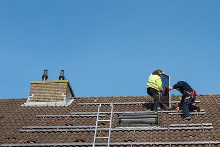 屋根の上の金属の建設に太陽電池パネルを置く男 写真素材
