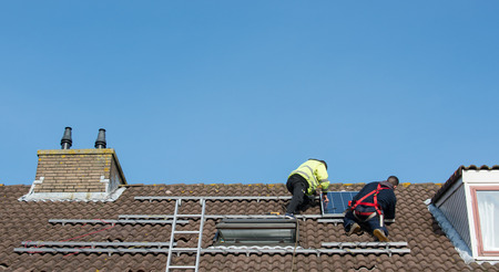 man putting the solar panel to the metal construction on the roof photo