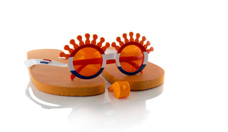 plastic glasses horn flute slippers  and flag in orange color and isolated on white photo