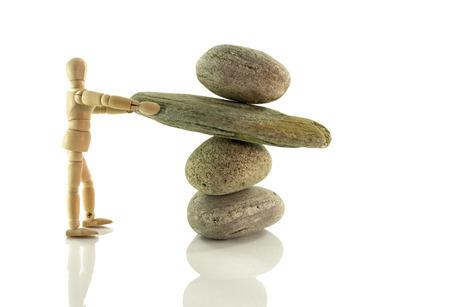 marioneta de madera: marioneta de madera sosteniendo rocas aisladas en blanco en perfecto equilibrio
