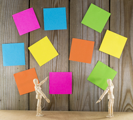 two wooden puppet man with wall full of sticky note  photo