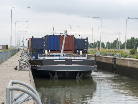 maas: cargo ship in the maas river lock in holland