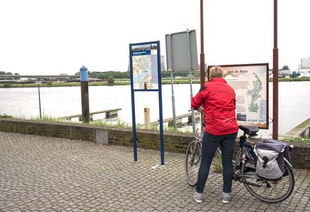 maas: woman looking at information board near the river maas in Holland