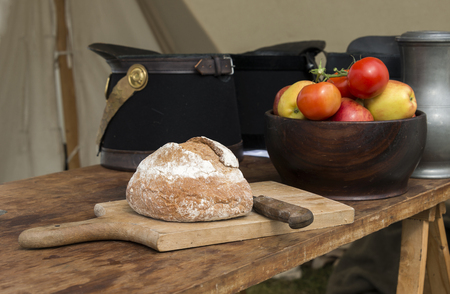 fresh bread and red tomatoes with soldiers caps on the background photo